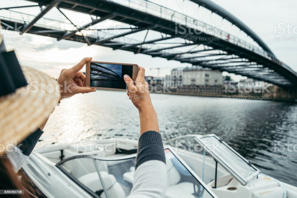 woman is taking picture while sitting on pier in the morning stock photo