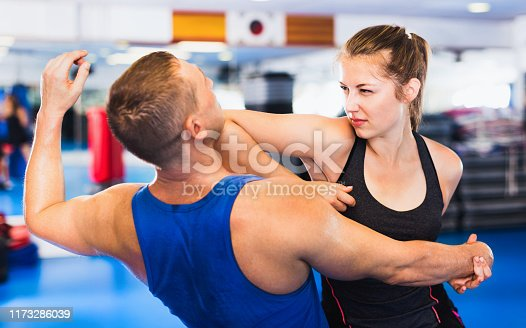 Bold  woman is training with man on the self-defense course in gym.
