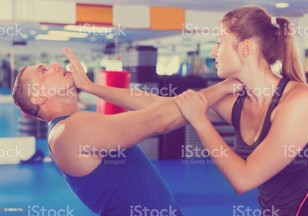 Mulher está treinando com o homem sobre o curso de defesa pessoal no ginásio. - foto de acervo
