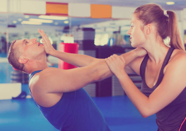 Woman is training with man on the self-defense course in gym. Strong bold positive woman is training with man on the self-defense course in gym. self defense stock pictures, royalty-free photos & images
