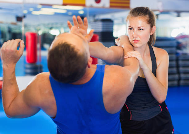 Woman is training with man on the self-defense course in gym. Strong bold  cheerful  woman is training with man on the self-defense course in gym. self defense stock pictures, royalty-free photos & images