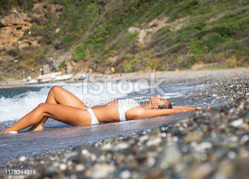Sunbath. Woman is lying on the coast.