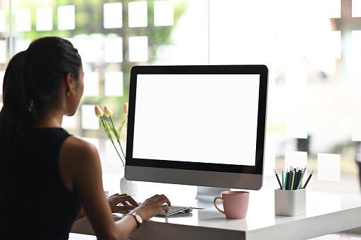 A woman is using a mockup computer with empty screen on modern workspace.