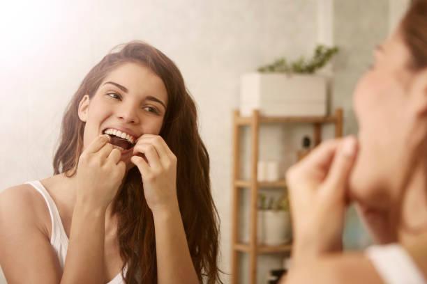 Woman is using dental floss stock photo