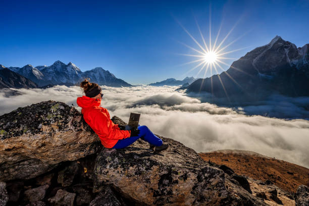 Woman  is using laptop during sunset over Himalayas, Everest Region stock photo