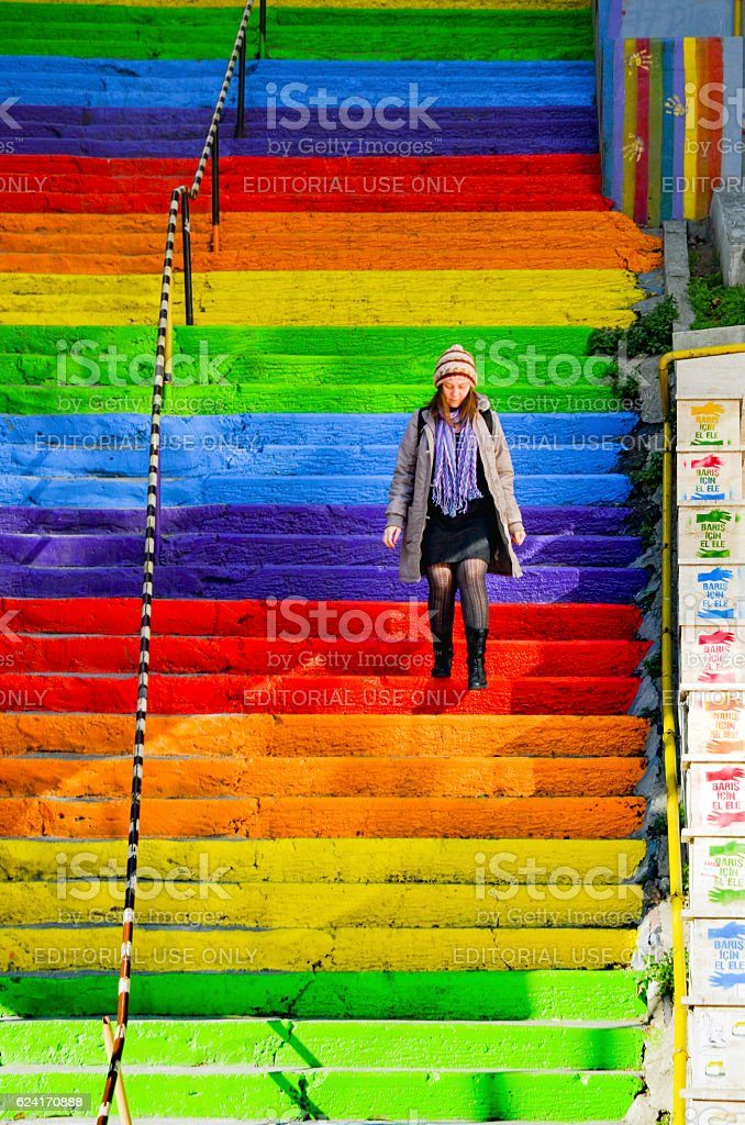 Woman is walking in the rainbow-colored stairs stock photo