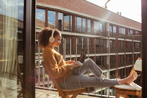 Young woman is using a laptop, working from the balcony of her apartment