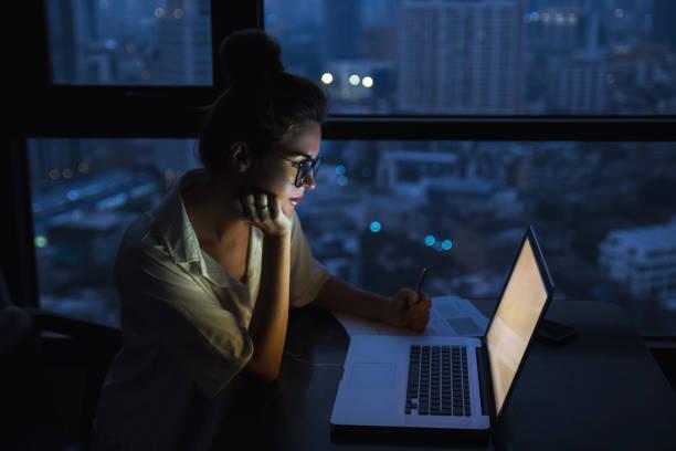 mujer está trabajando con el portátil en casa durante la noche. - trabajar hasta tarde fotografías e imágenes de stock