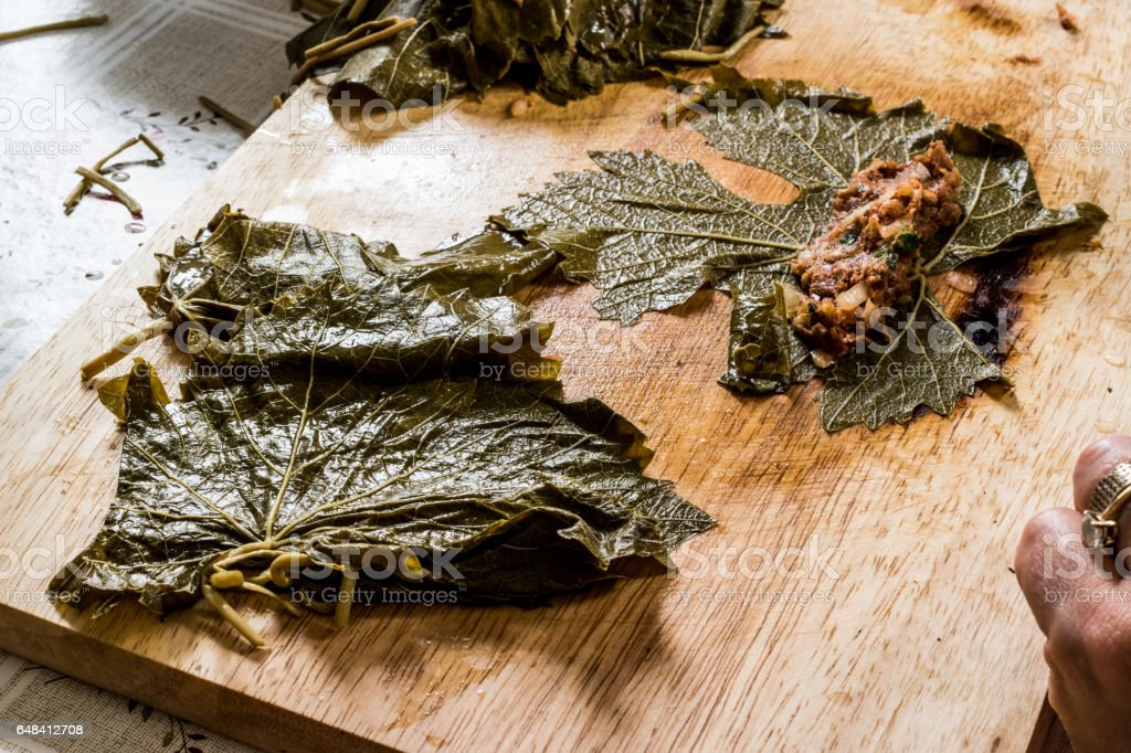 Woman is wrapping grape leaves for turkish dolma with minced meat. stock photo