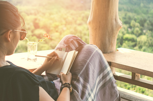 Woman is writing down in small white memo notebook for take a note plan to do or write a book with beautiful terrace of house and nature mountain view background.