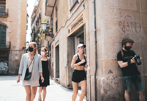 Barcelona, Spain - June 5, 2021: Woman jogger passes by unmasked tourists in pandemic