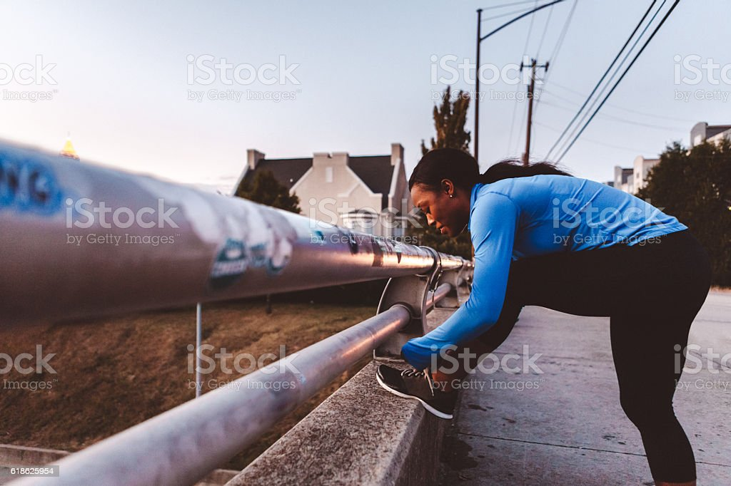 woman jogger stopping to tie shoes stock photo