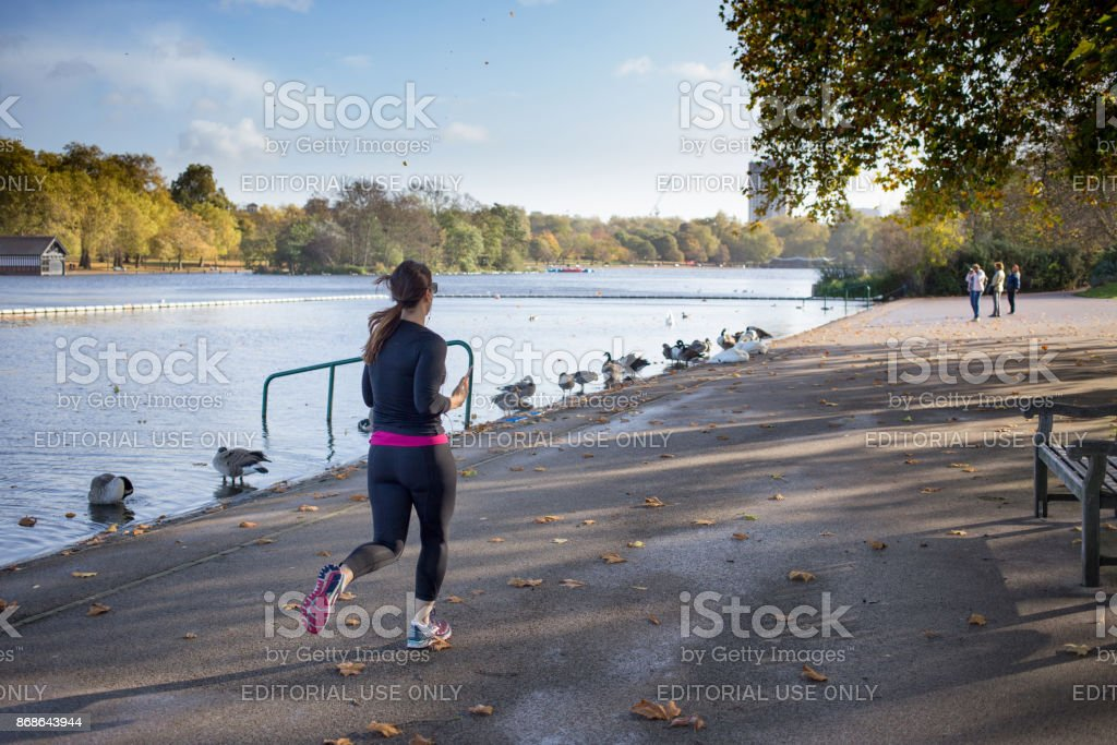 Woman Jogging along the shorline of The Serpentine Lake in Hyde Park, London, UK on a sunny Autumn morning stock photo