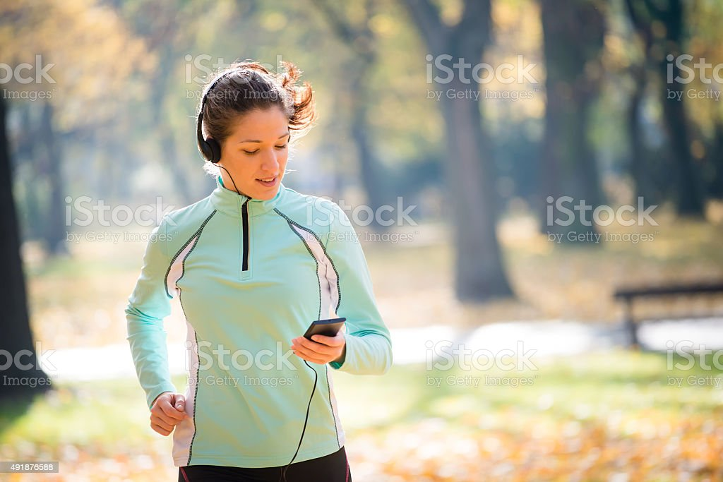 Woman jogging and listening music stock photo