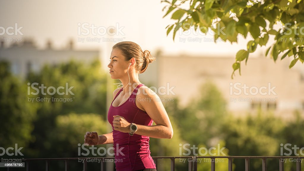 Woman jogging and listening songs stock photo