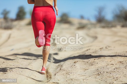 Young woman jogging away on sand, close up