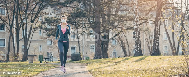 Woman jogging down a path boosting her immune system and fitness for covid-19