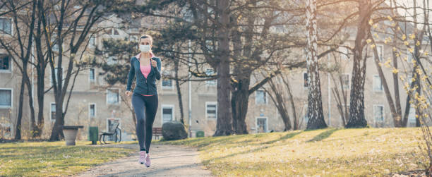 Woman jogging down a path boosting her immune system for covid-19 stock photo