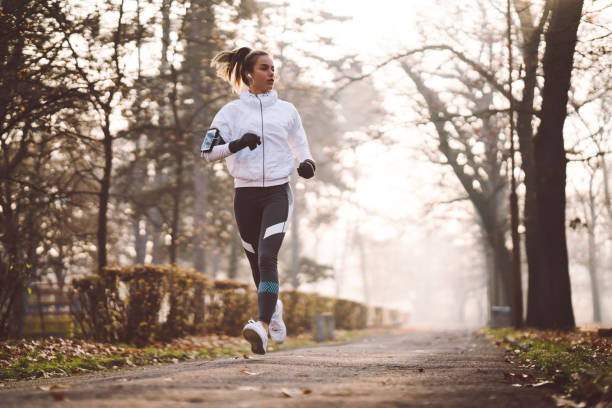 Woman jogging during winter morning Sports woman exercising among nature in a winter day running stock pictures, royalty-free photos & images