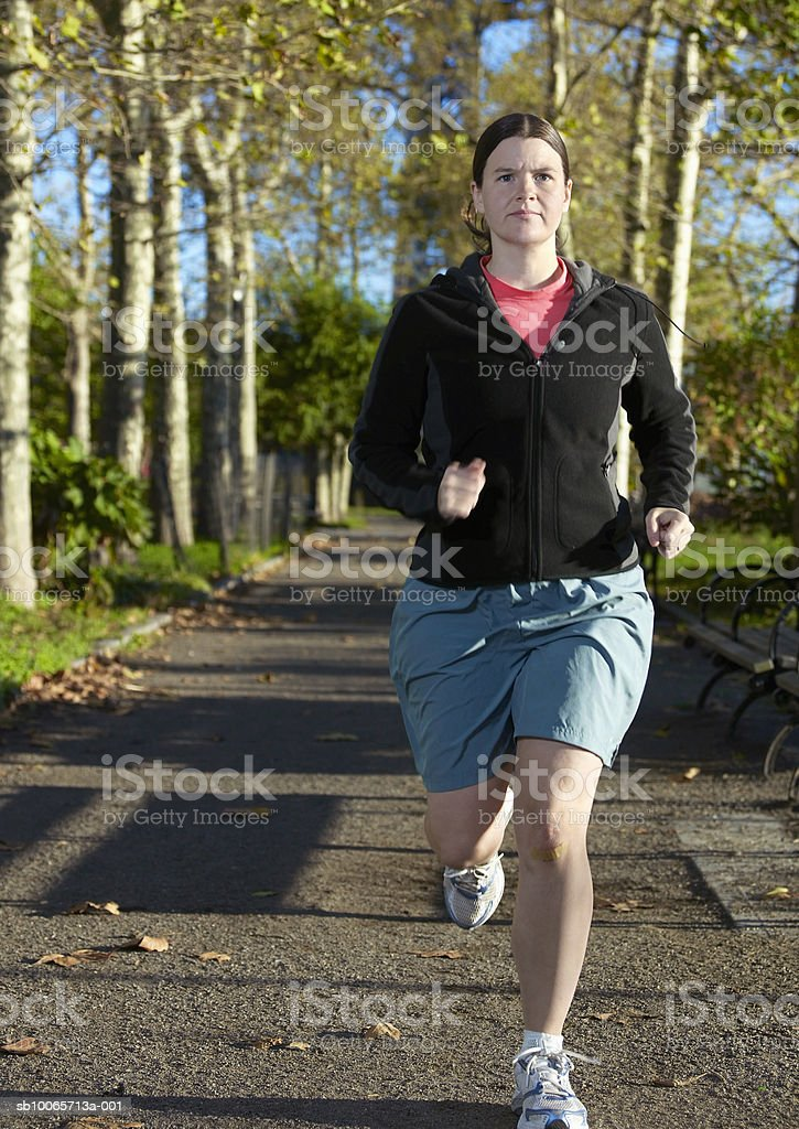 Woman jogging in park royalty free stockfoto