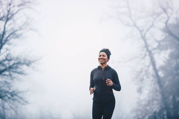 A woman jogging in the park on a misty day. She is smiling. She wears headphones and sports clothes. stock photo