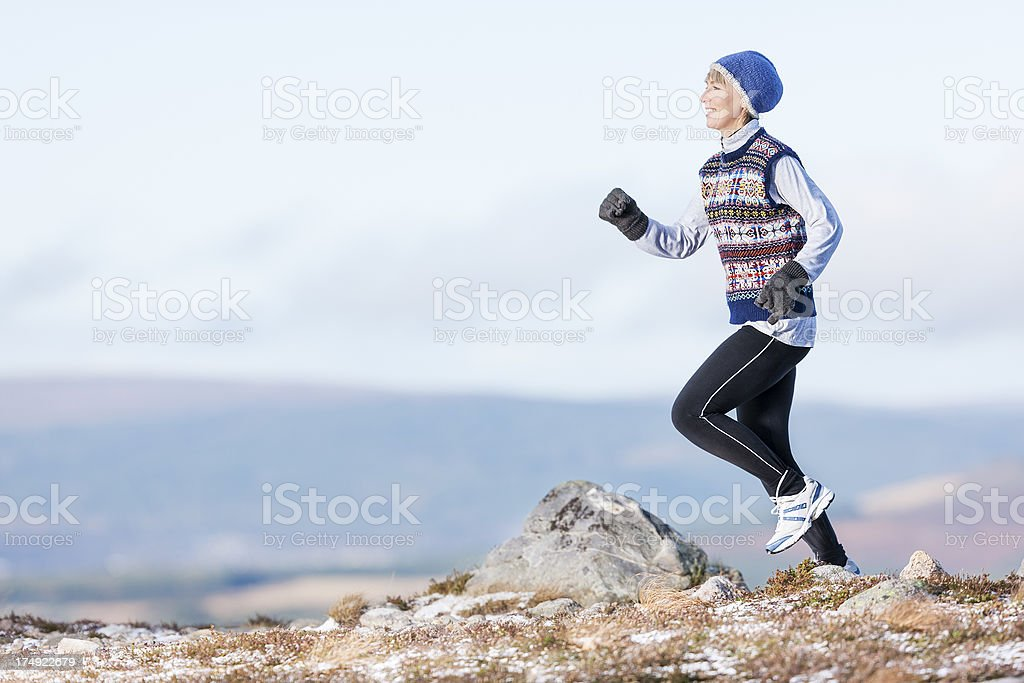 Woman jogging in winter in mountains stock photo