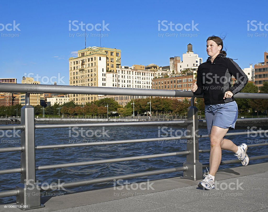 Woman jogging on bridge royalty-free stock photo