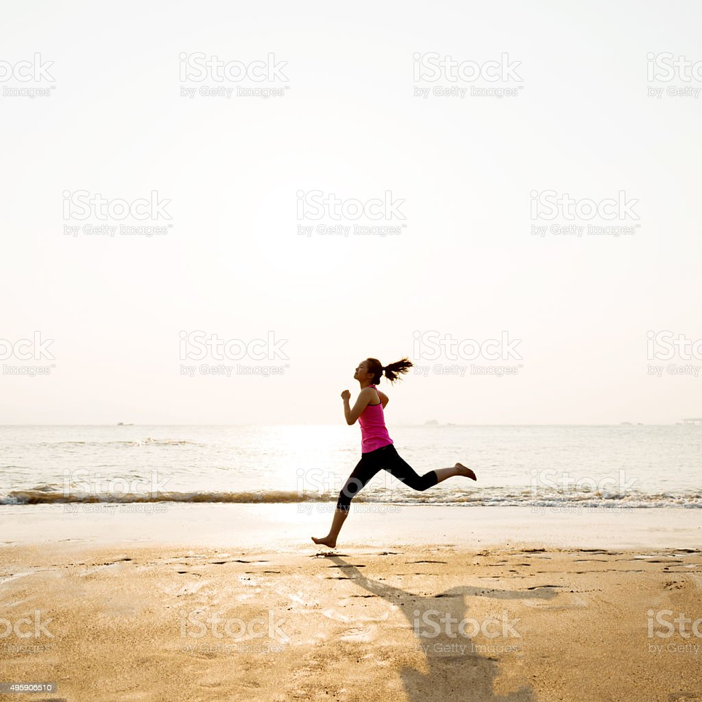 Woman jogging on shore at sunrise stock photo
