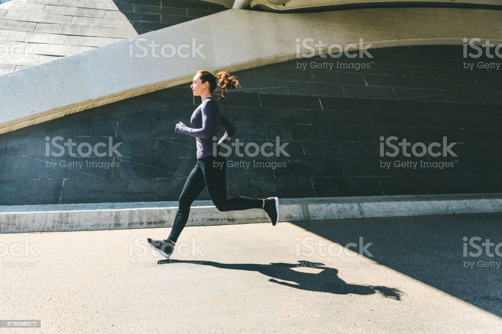 Woman jogging or running, side view with shadow royalty-free stock photo