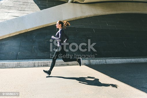 istock Woman jogging or running, side view with shadow 916586372