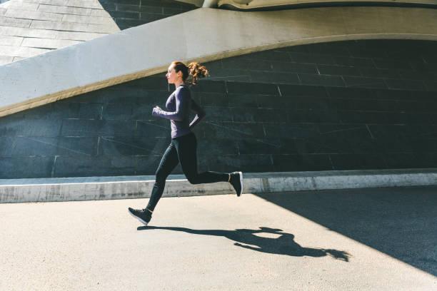 frau, joggen oder laufen, seitliche ansicht mit schatten - joggerin stock-fotos und bilder