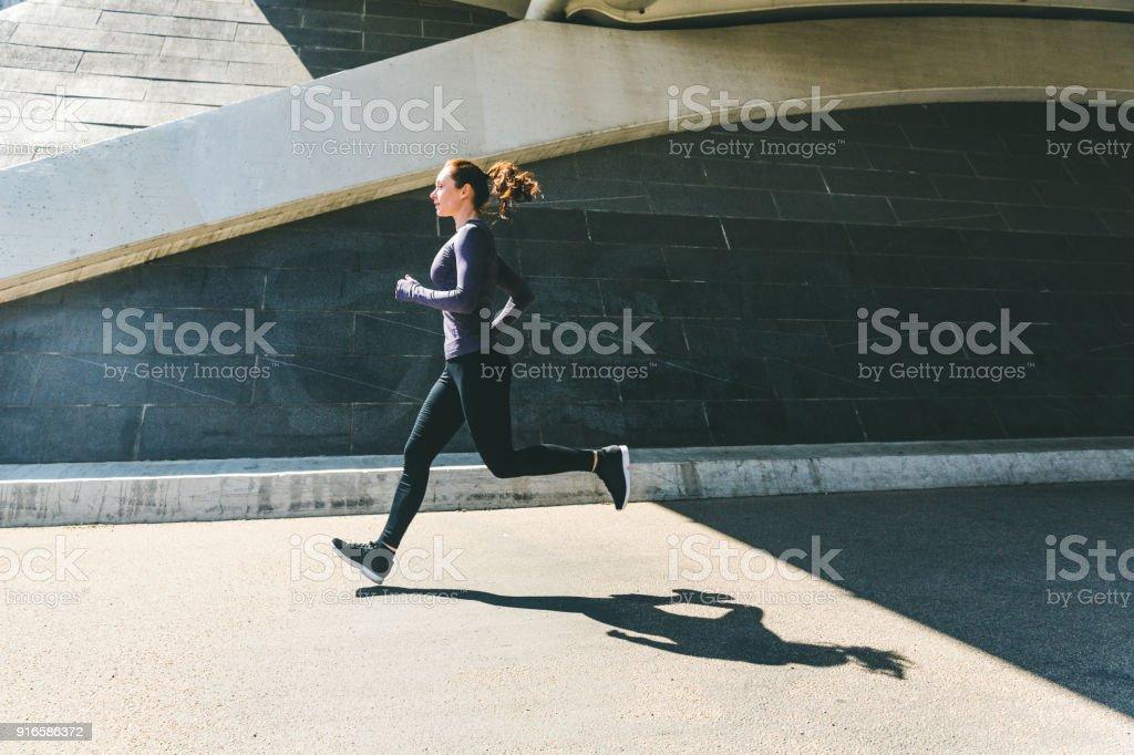 Frau, Joggen oder laufen, seitliche Ansicht mit Schatten – Foto