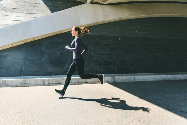 Woman jogging or running, side view with shadow stock photo