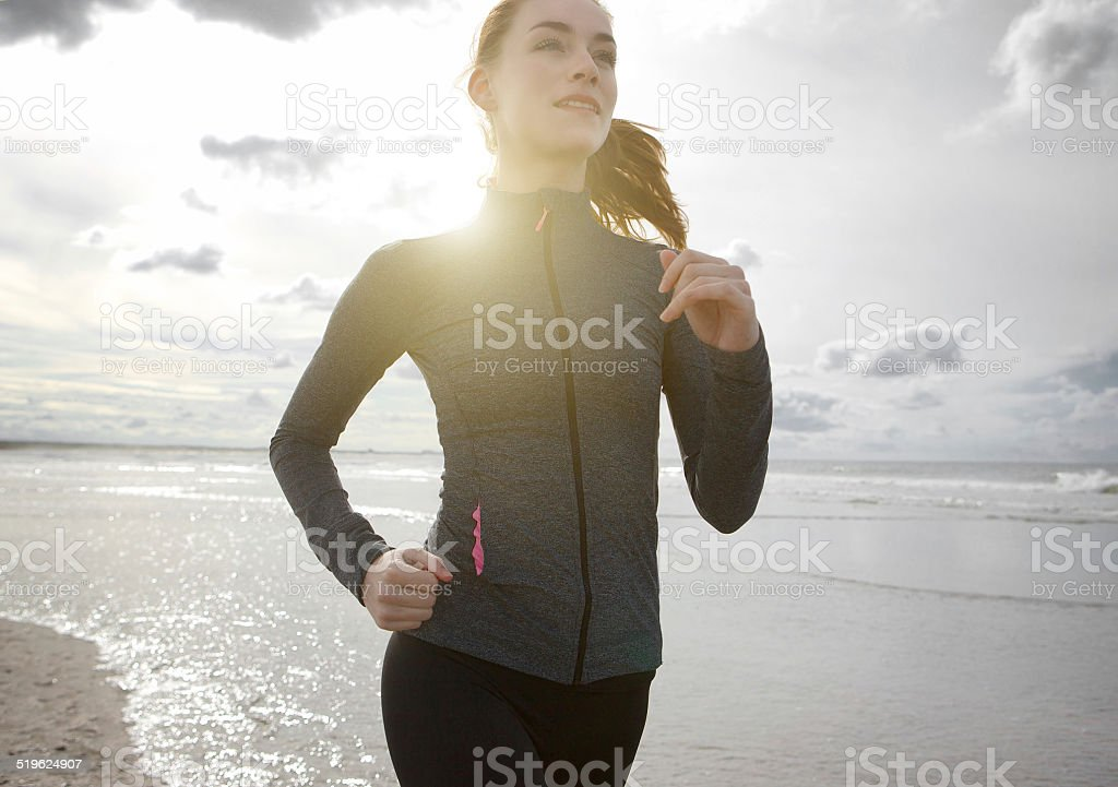 Woman jogging outdoors by the beach stock photo