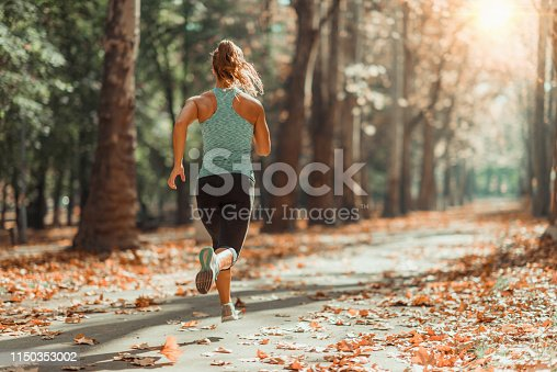 Woman Jogging Outdoors In Autumn in Public Park