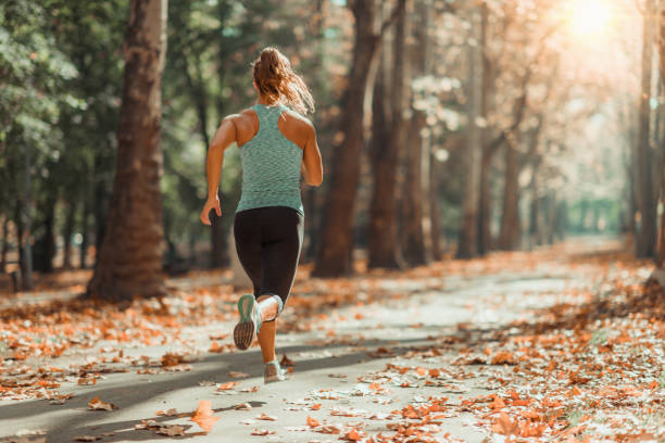 Woman Jogging Outdoors in The Fall Woman Jogging Outdoors In Autumn in Public Park running stock pictures, royalty-free photos & images