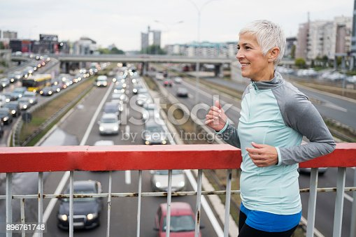 istock Woman jogging outdoors 896761748