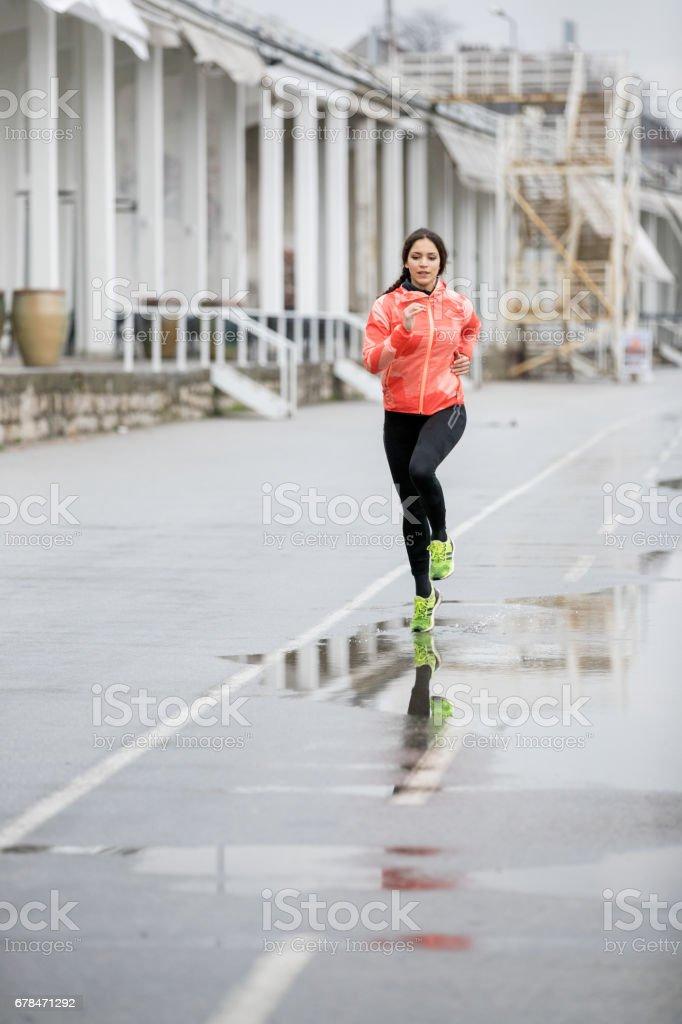 Woman jogging through puddles royalty-free stock photo