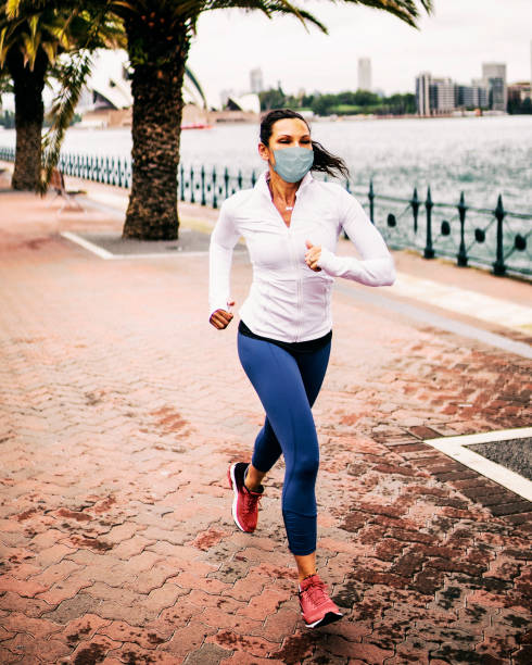 Woman jogging wearing healthcare mask for protection. stock photo