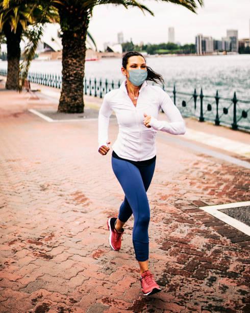 Frau joggt mit Gesundheitsmaske zum Schutz. – Foto