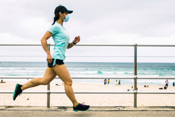Woman jogging wearing healthcare mask. stock photo