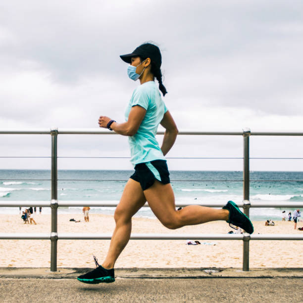 Frau joggt mit Gesundheitsmaske. – Foto