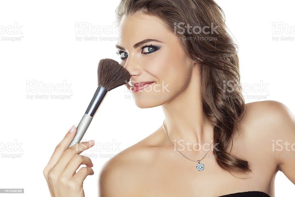Woman joking with a make-up brush royalty-free stock photo