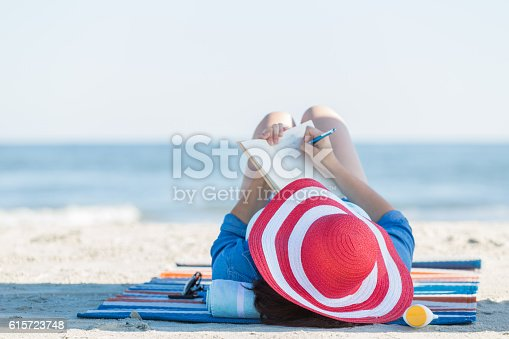 Peaceful woman writes in her journal while lying on the beach during a beach vacation. she is wearing a red and white striped straw hat. The ocean is blurred in the background.