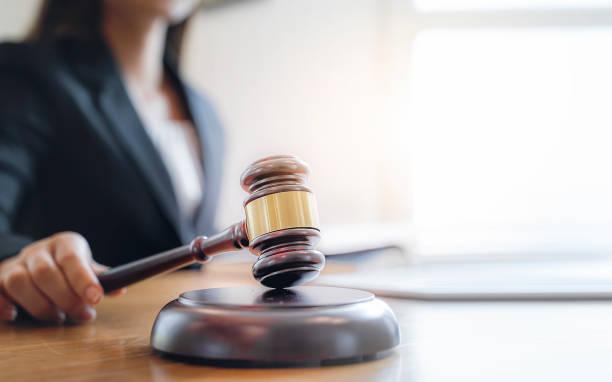Mujer juez mano sosteniendo el mazo para golpear el bloque de sonido en la sala de la corte. - foto de stock