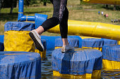 A woman jumping across a blue and yellow obstacle course, leaping from point to point, as large inflatable arms try and knock her into the water below. She is wearing black leggings and white coloured sports shoes. She is trying to catch up her team mates who are running ahead and can be seen in the background running up a grassy hill