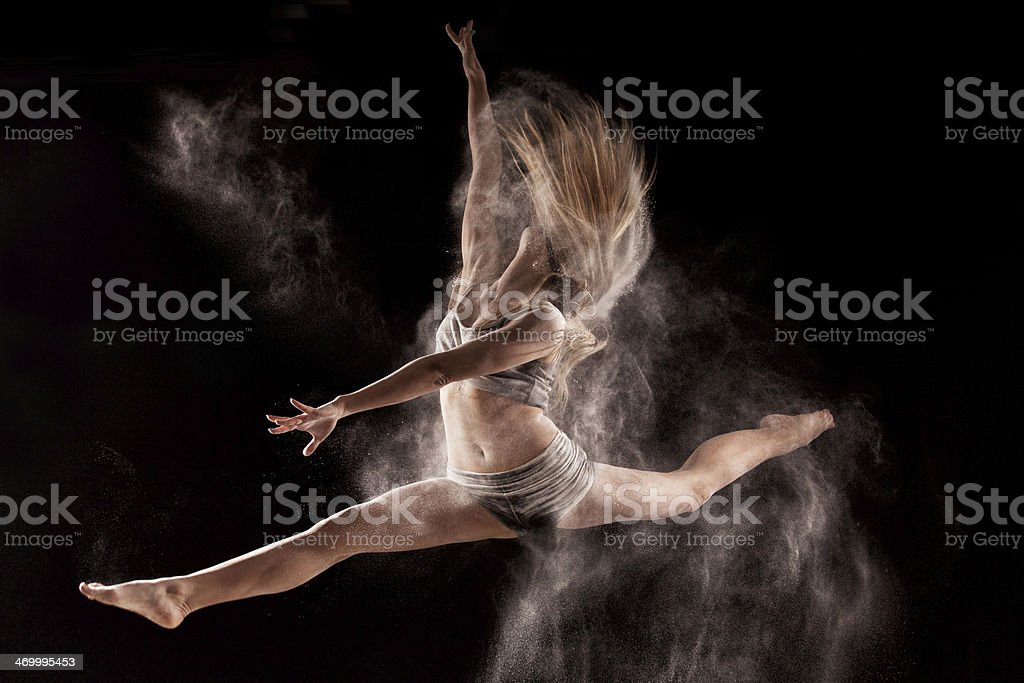 Woman jumping and dancing in a cloud of  powder stock photo