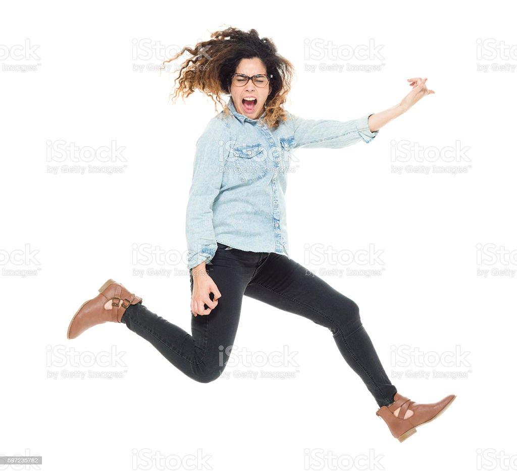 Woman jumping and playing air guitar stock photo