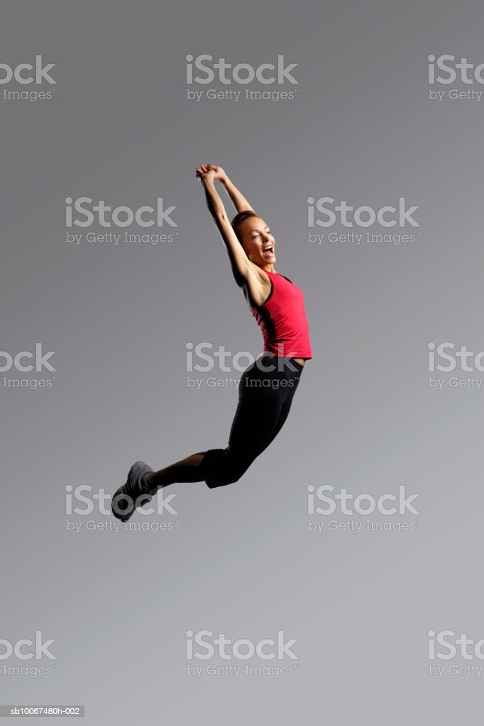 Woman jumping, arms up foto de stock libre de derechos