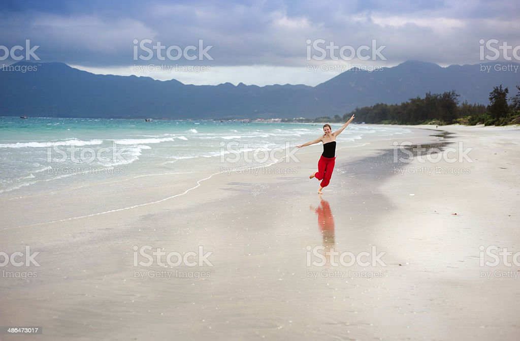 Woman jumping at the beach. stock photo